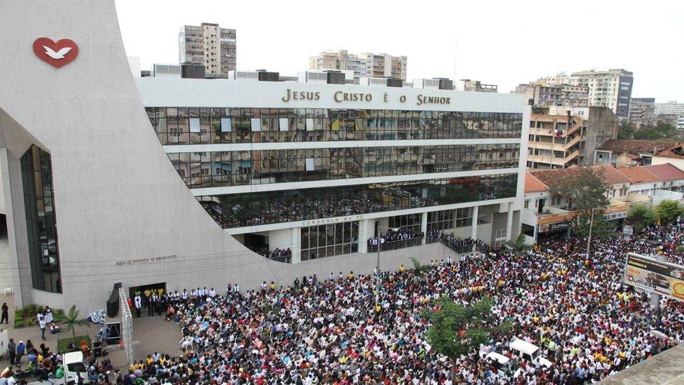 Edificio de la Iglesia Universal en Maputo rodeado de cientos de fieles