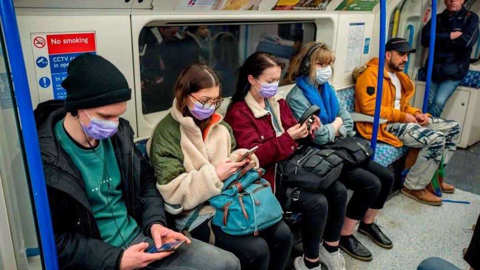 Gente con mascarillas en el metro de Londres.