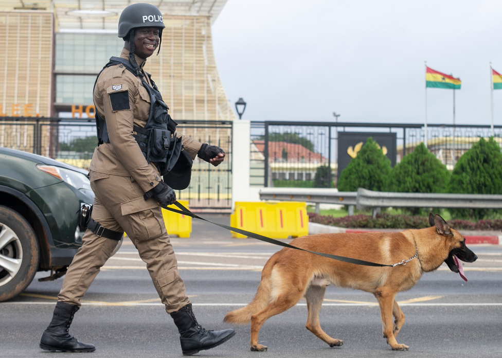 A Ghana policeman walks with his dog during a confidence building march through the streets of capital Accra, Ghana 21 September