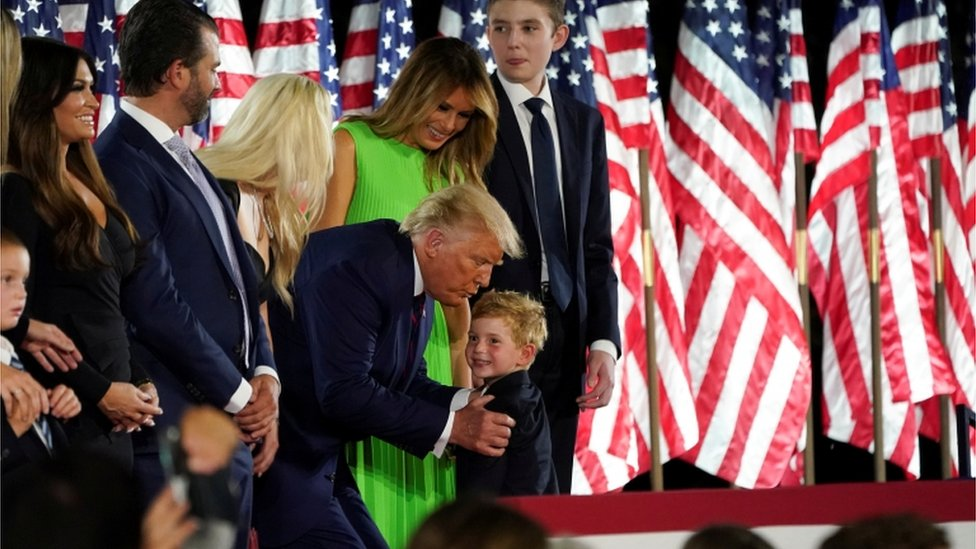 U.S. President Donald Trump grabs one of his grandchildren as he, U.S. first lady Melania Trump and their extended family