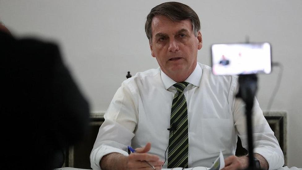 Bolsonaro, sentado diante de mesa, fala para câmera de celular