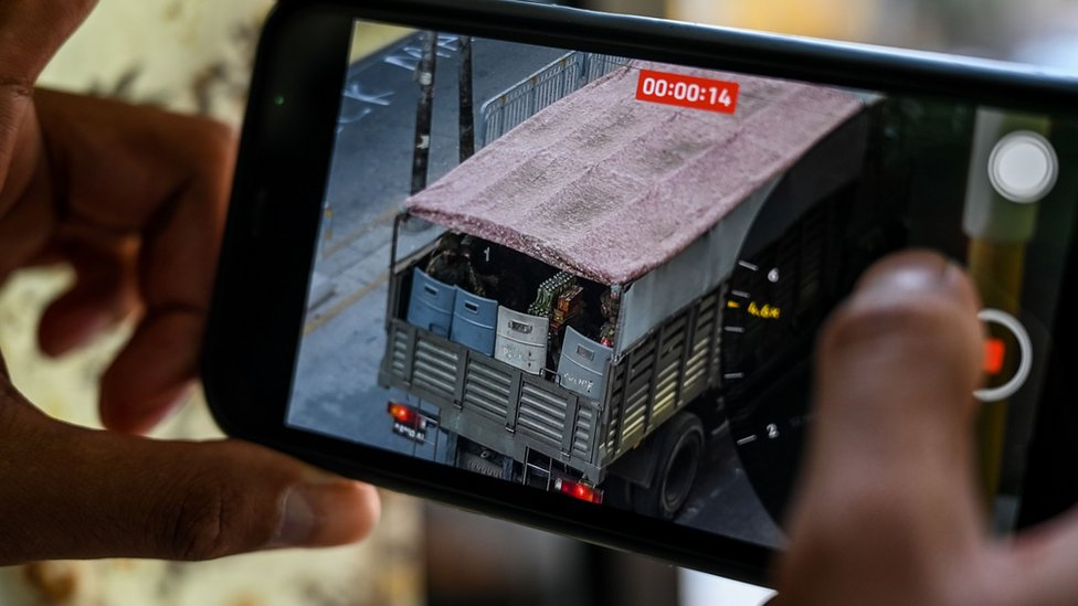 A person holds a mobile phone showing a video of soldiers looking out from a truck in Yangon on February 28, 2021