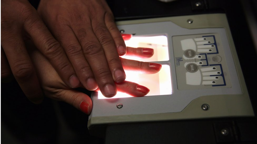 A Chinese immigrant is fingerprinted during her 'biometrics' appointment to receive a green card at the U.S. Citizenship and Immigration Services (USCIS).