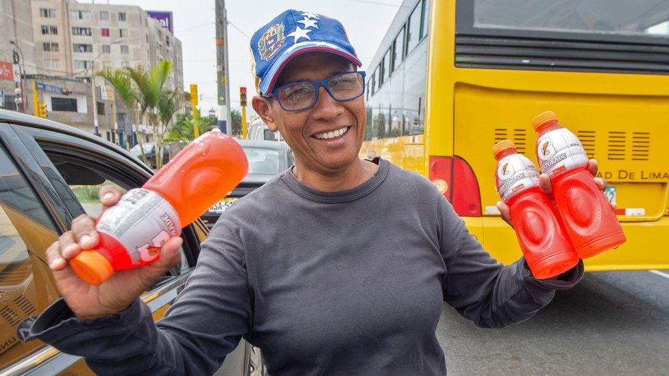 Venezuelan Mari Alvarez sells cold drinks while vehicles stop at a traffic light in Lima on April 4, 2019.