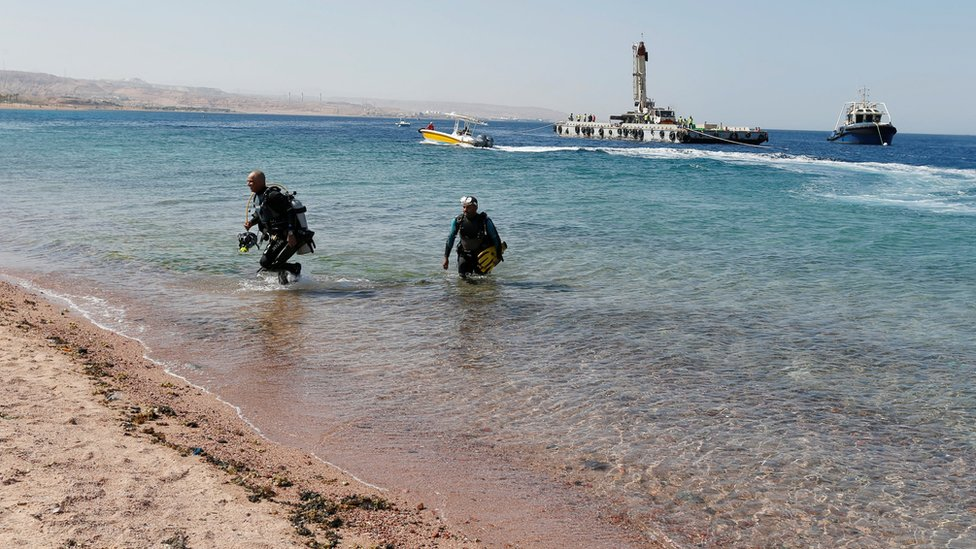 Divers get out of the water after the submerging of military vehicles in the Red Sea off Aqaba