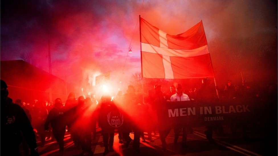 Manifestantes com uma grande bandeira da Dinamarca cruzam a capital Copenhague