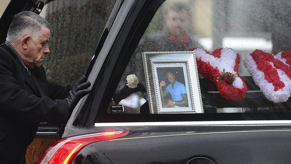 An undertaker puts a flower on Jim Donegan's coffin