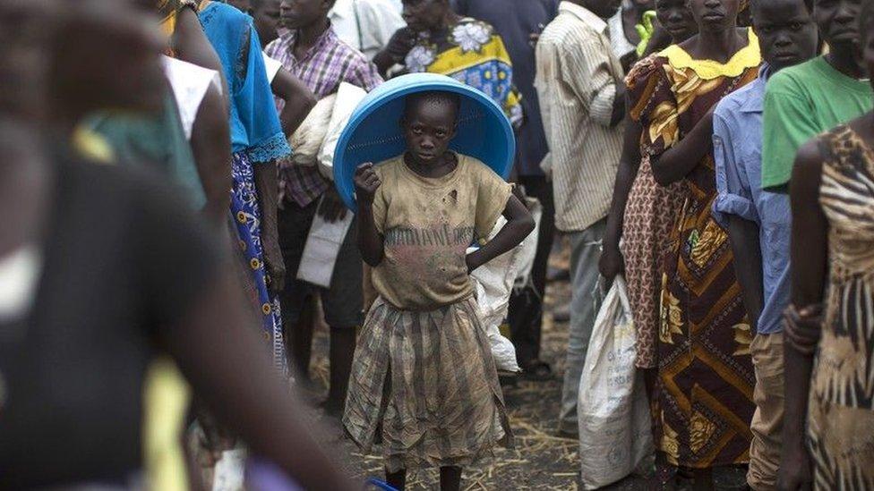 Niño mirando a la cámara en un grupo de adultos