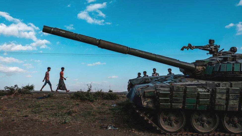 شبّان يسيرون بجوار دبابة مهجورة تابعة لقوات تيغراي جنوب بلدة مهوني، إثيوبيا