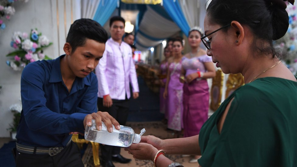A man shares hand sanitiser with a woman at a wedding service in Cambodia