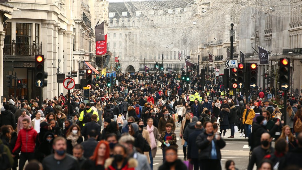 Crowds fill a pedestrianised Regent Street, walking under street decorations of angels installed for Christmas
