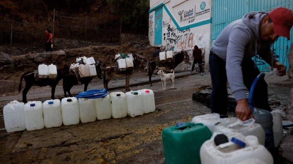 Residente de Xochimilco, en Ciudad de México, rellena botellones de agua el 20 de abril del 2021