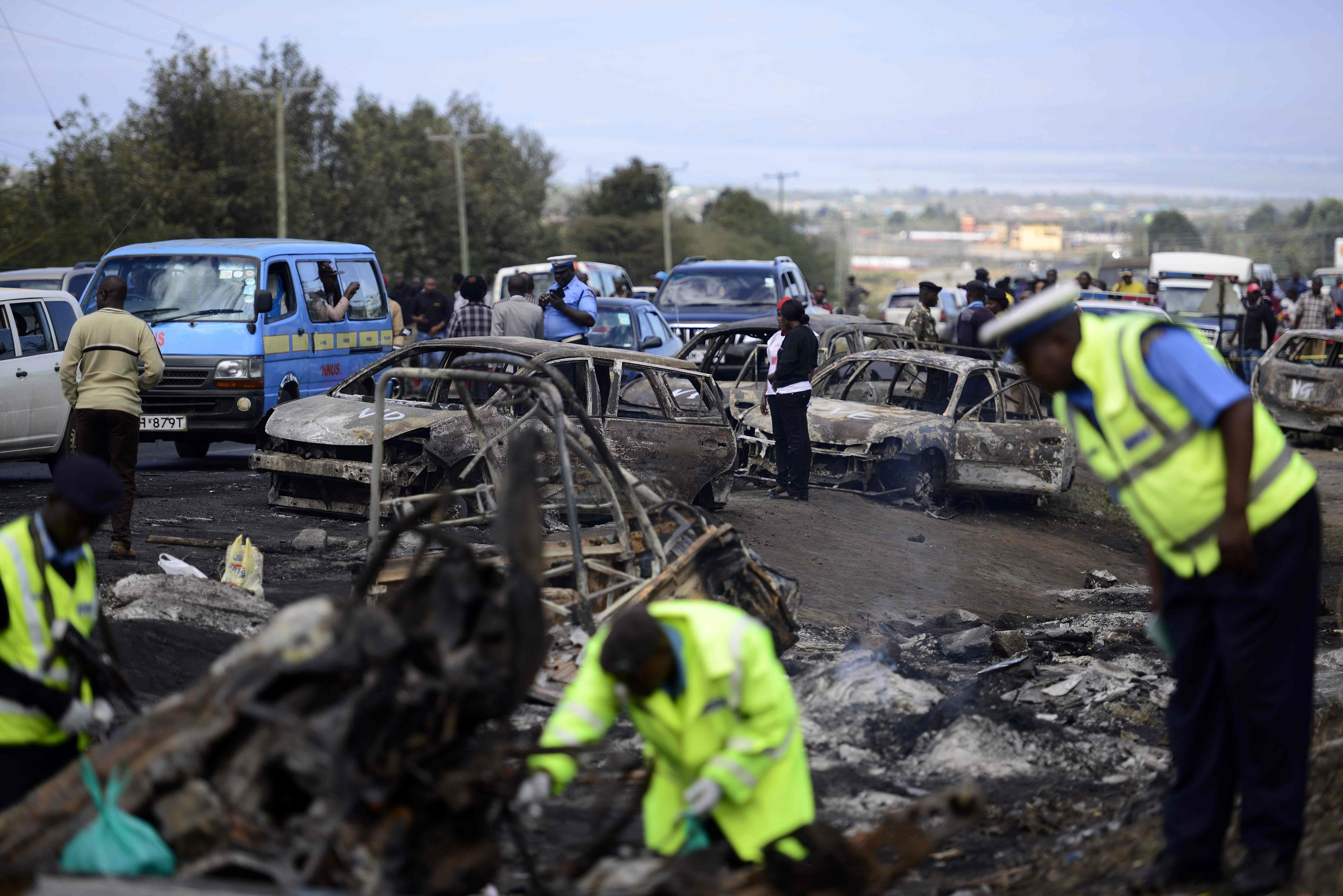 Kenyan police officers search for the remains of victims at the crash site of a truck that rammed into several vehicles before bursting into flames near Karai on the busy Naivasha highway,