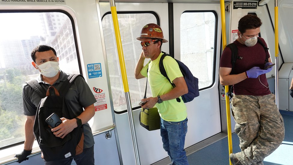 People, some wearing protective masks, ride the Metromover as they try to protect themselves against the coronavirus on 24 March 2020 in Miami, Florida.