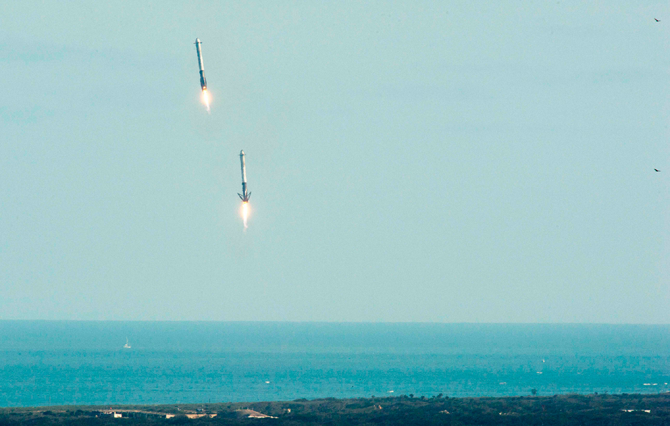 Falcon Heavy's booster rockets descend to land at Florida's Space Coast