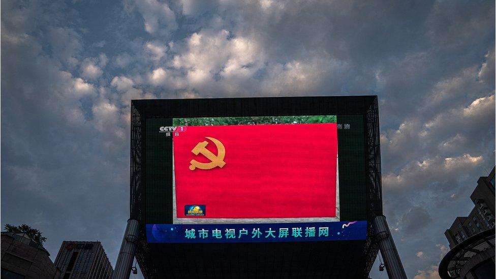 北京街頭一台大型戶外屏幕在直播的中國中央電視台《新聞聯播》中展示著一面中國共產黨黨旗(1/7/2020)