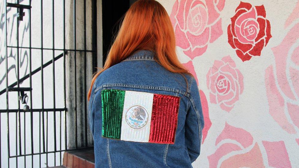 Patty Delgado de espaldas con una chaqueta con la bandera de México