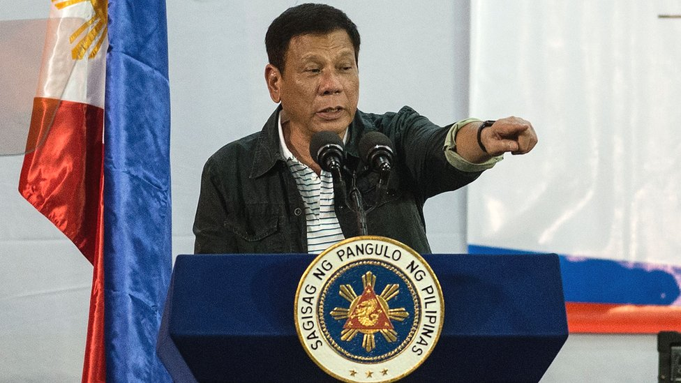 Philippine President Rodrigo Duterte gestures to a crowd at a conference, 30 June 2016