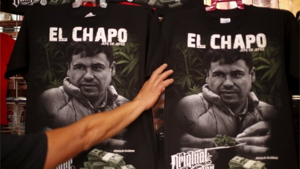 """T-shirts with an image of Joaquin """"El Chapo"""" Guzman for sale in a market"""