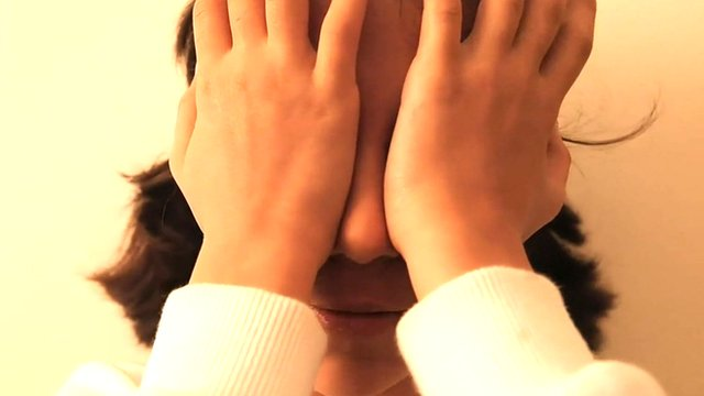 A girl covering her eyes
