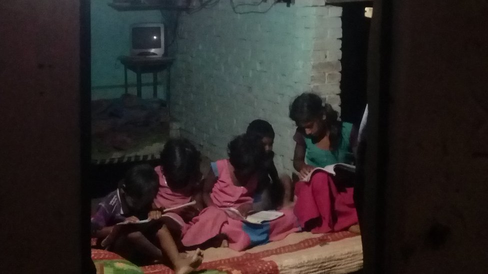 Children reading under a solar light