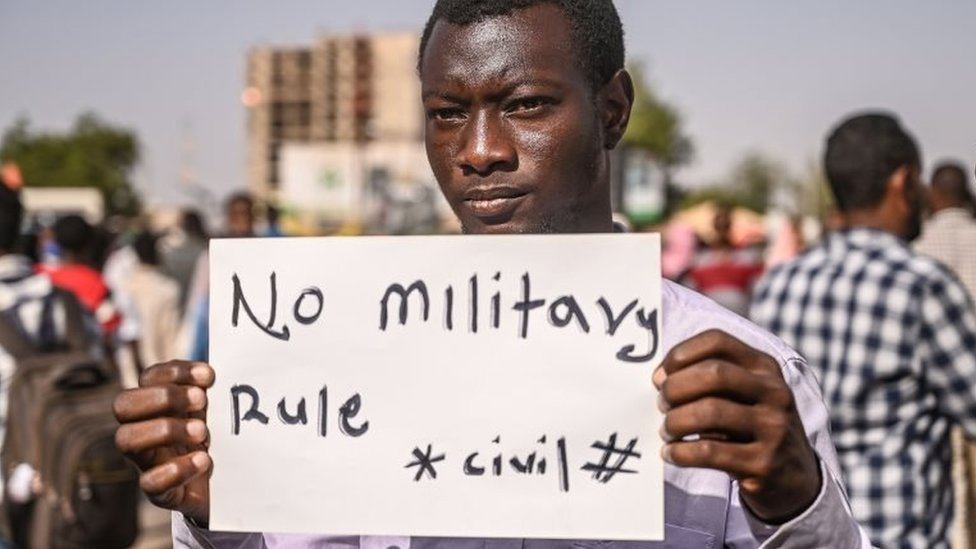 A Sudanese protester holds a placard during a sit-in outside the army headquarters in the capital Khartoum on 29 April 2019