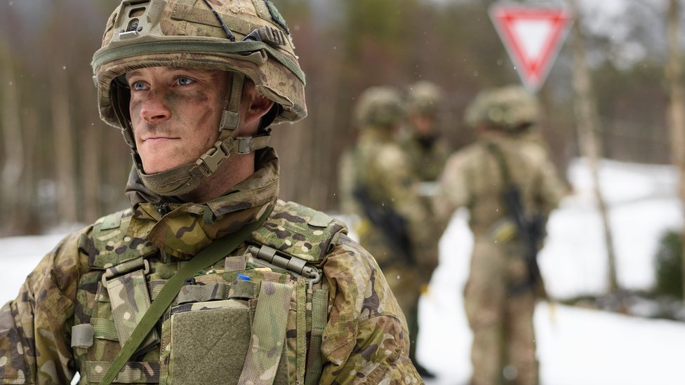 A member of the British Army Royal Irish Regiment B Company stands guard as obstruction tactics are discussed