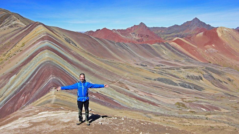 Turista parado de espaldas a la Montaña de los Siete Colores.