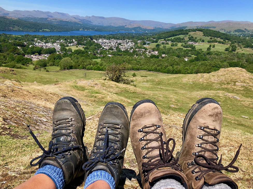 Couple's hiking boots and view of Lake Windermere