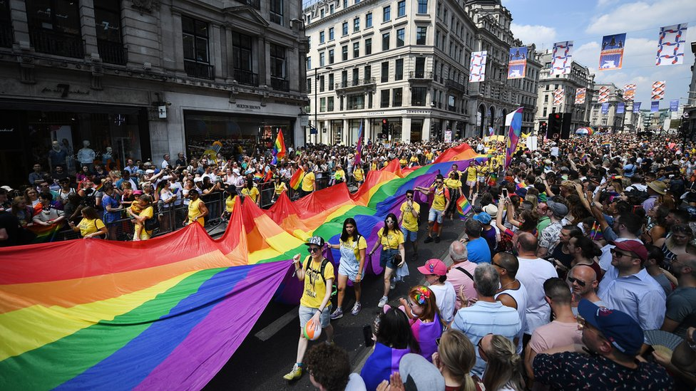 Participants carry a giant Rainbow flag as tens of thousands of people attend the annual London Pride Parade in
