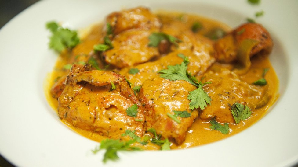 A plate of Chicken Tikka Masala curry in a restaurant