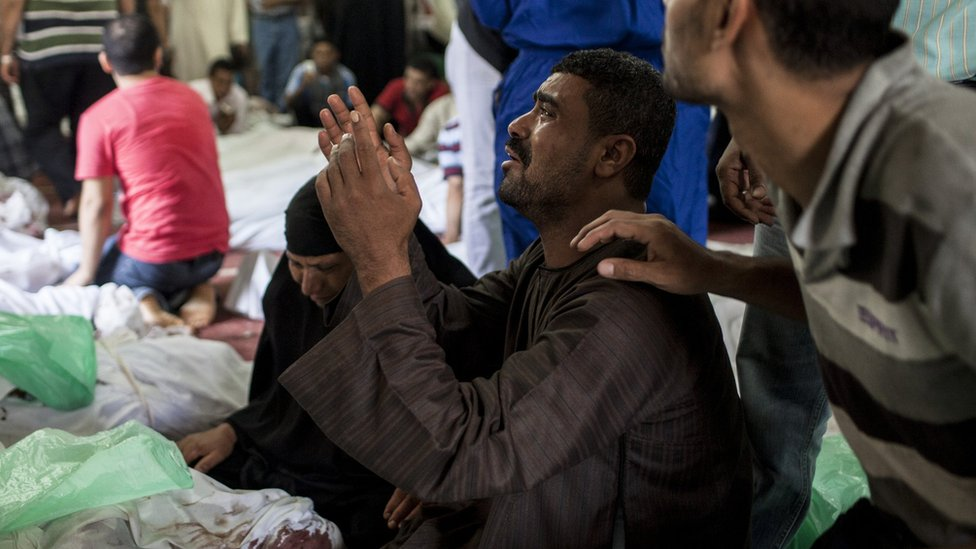 An Egyptian man identifies the body of a family member killed during a crackdown by Egyptian security forces in Cairo, Egypt (15 August 2013)