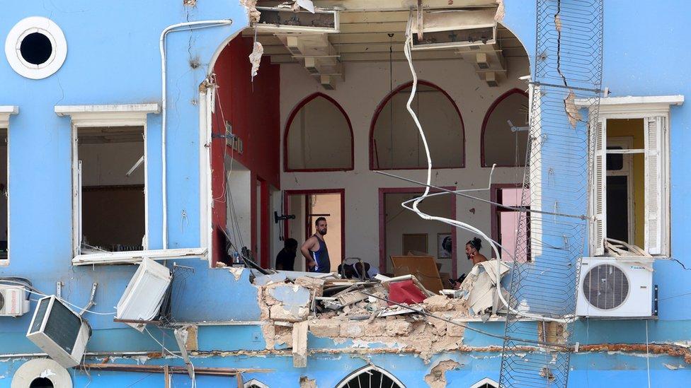 Men inspect a damaged building near Beirut's port area (6 August 2020)