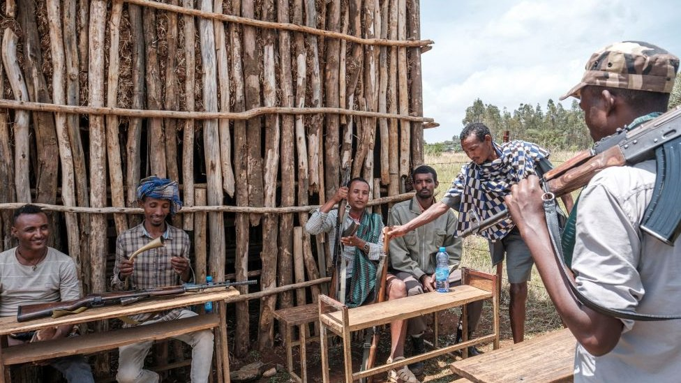 عناصر من ميليشيا الأمهرة يستريحون بجوار مركز اقتراع في قرية ويرب ميخائيل، وهي منطقة ريفية تبعد 15 كيلومتراً من بحر دار، إثيوبيا. 21 يونيو/حزيران 2021.