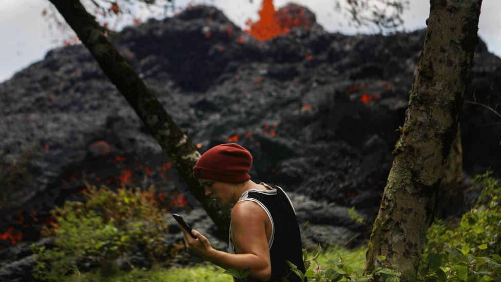 A man looks at his phone while walking in front of an eruption