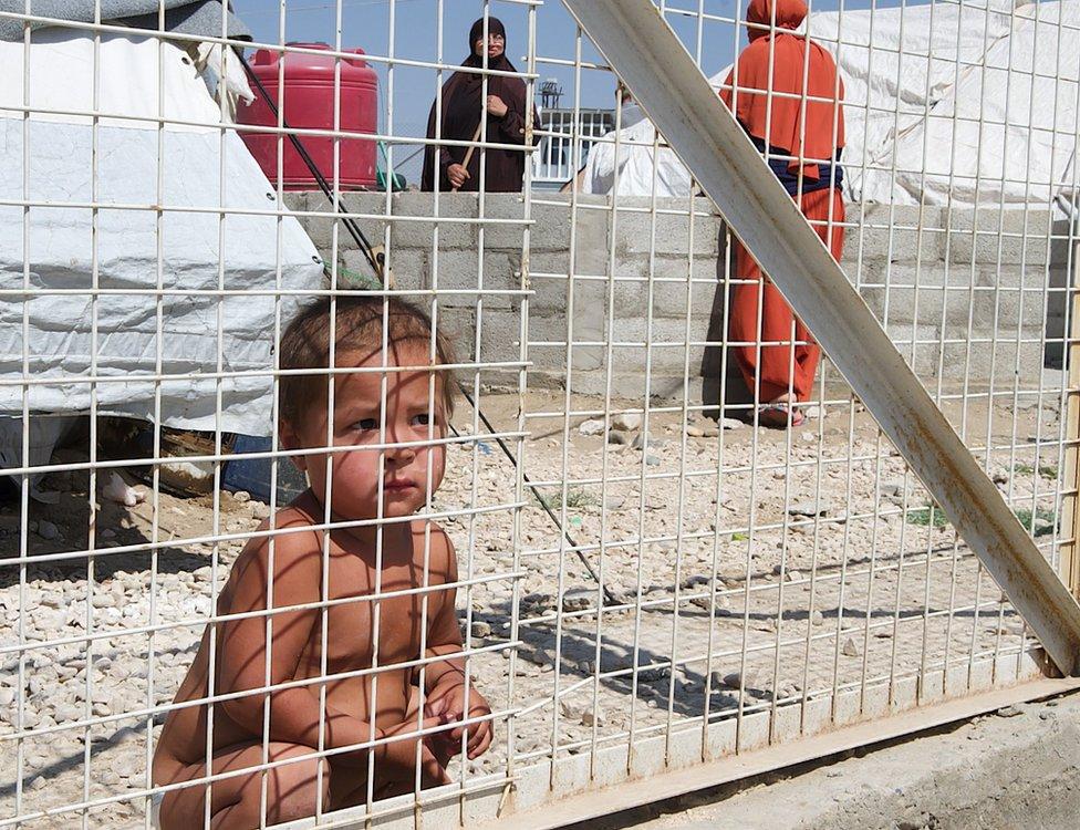 طفل يجلس خلف السور في المخيم
