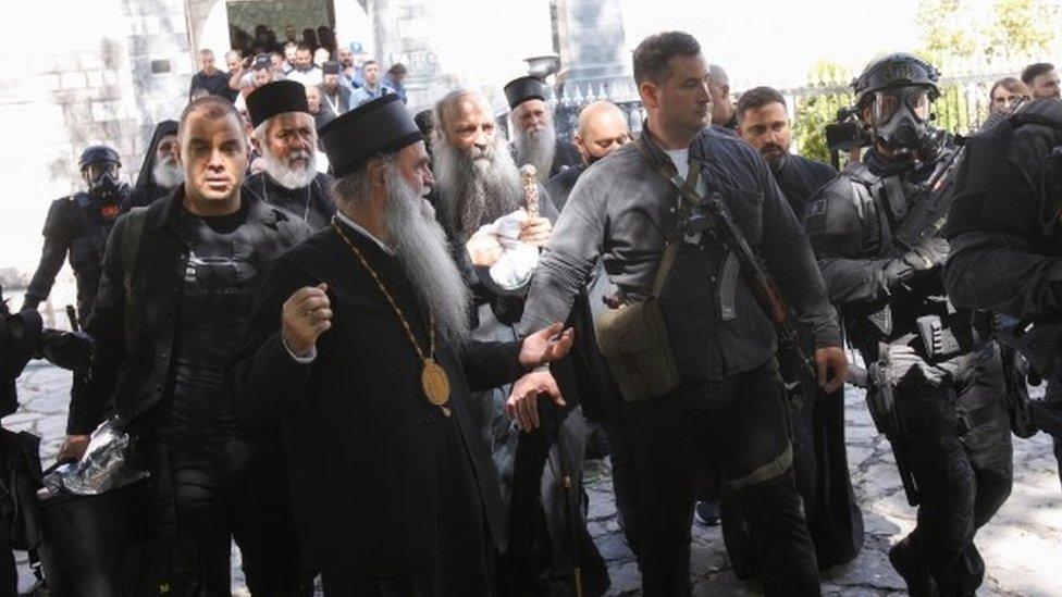 Security personnel escort Patriarch Portfirije and Bishop Joanikije outside a monastery in Cetinj