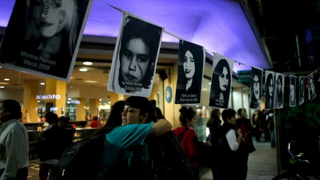 Two women embrace under pictures of victims of gender violence during a demonstration demanding policies to prevent femicides in Buenos Aires