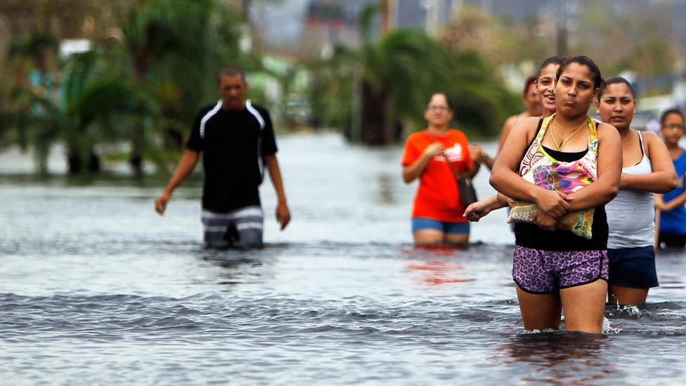 Personas caminando en un calle con el agua por las rodillas en Puerto Rico luego del Huracán María