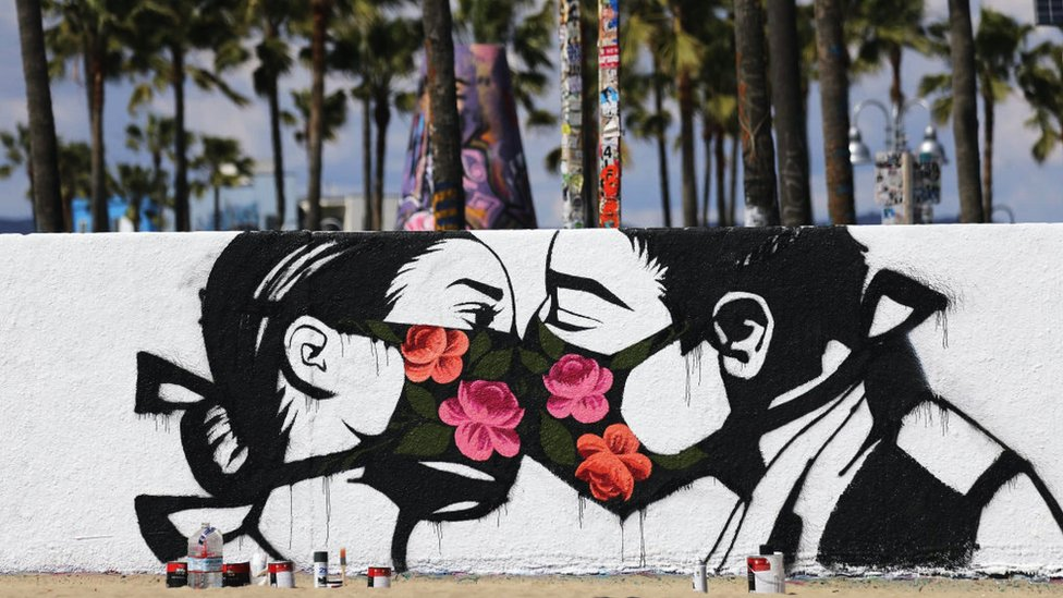 A graffiti of a couple wearing facemasks kissing