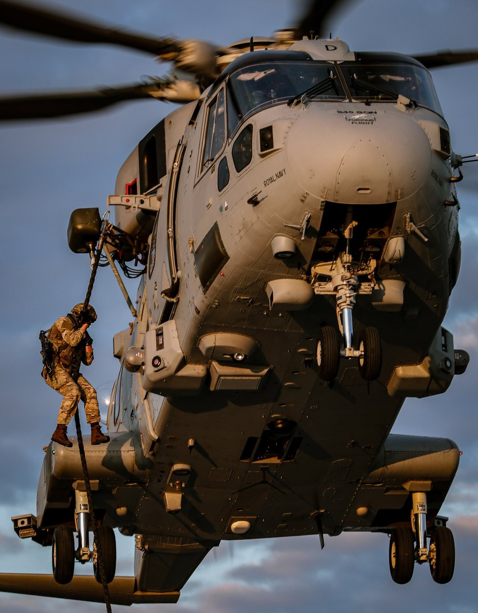 A Royal Marine dangles from a helicopter from a rope