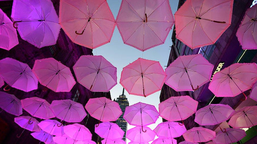 Calle adornada por completo con paraguas rosas
