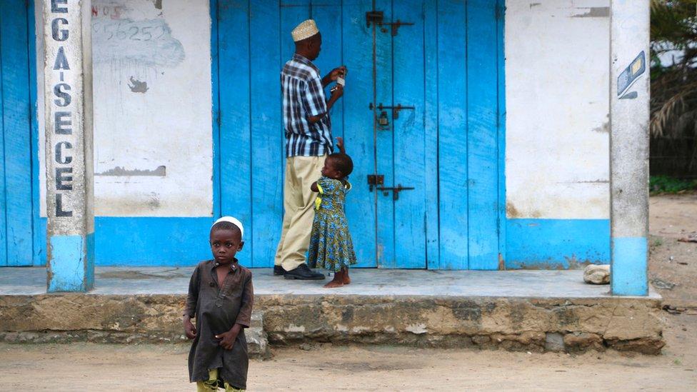 A shop owner closes down his shop on March 7, 2018 in Mocimboa da Praia, Mozambique