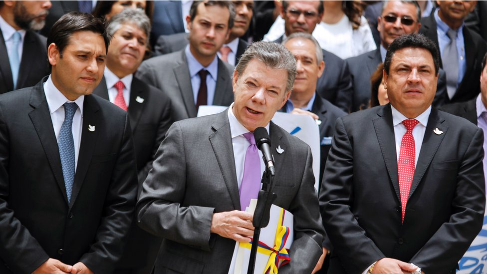 Colombia's President Santos (c) holds a copy with the final text of the peace agreement with the Farc