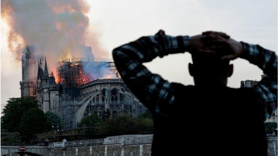 Un hombre mira el incendio en Notre Dame