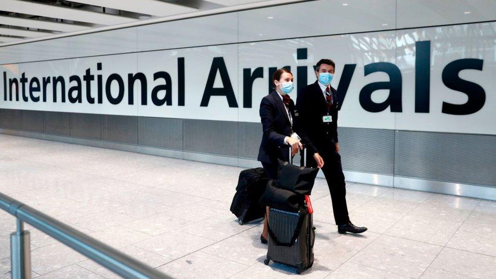 British Airways flight crew wearing masks walk through Heathrow Airport