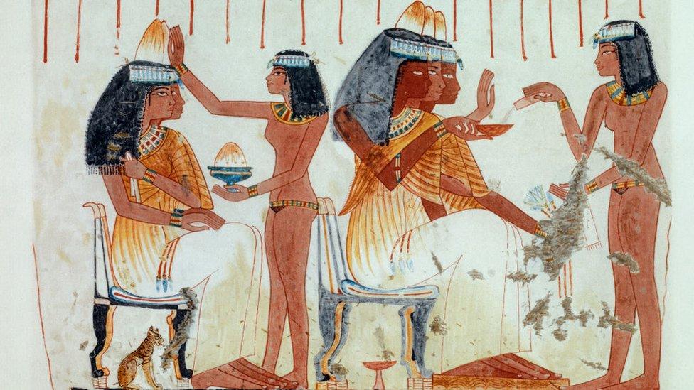 مقبرة نب آمون لخادمة تصب الزيت العطري في أقماع العطور وفتاة أخرى تحضر الدهن العطري على رؤوس مدعوات إلى حفل