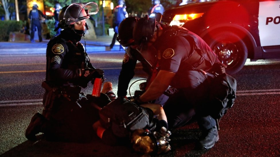 Police officers detain a demonstrator during a protest against police violence and racial injustice in Portland, Oregon, US