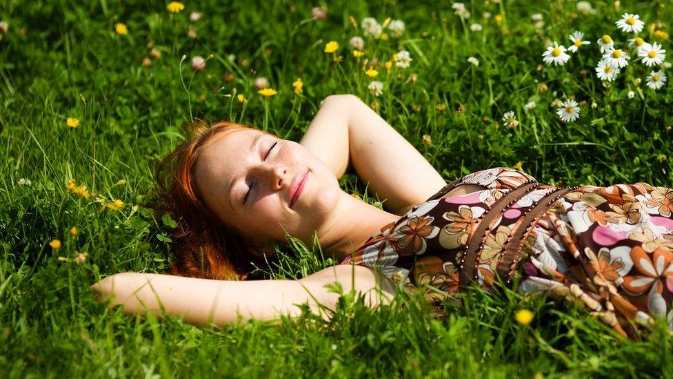 Una joven recostada en el pasto.