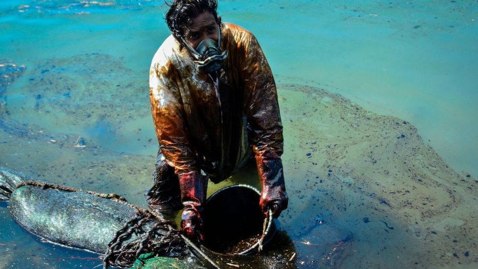 A man scoops leaked oil from the vessel MV Wakashio on 8 June.